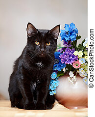 The black cat sits near a small vase with the flowers. - The...