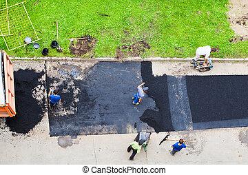 workers laid asphalt on road - workers laid asphalt on urban...
