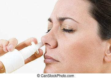 Nasal Spray - A young woman using nasal spray