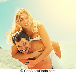 happy couple in love hugging and laughing on the beach -...