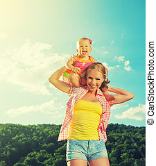 happy family. mother and daughter baby girl playing on nature