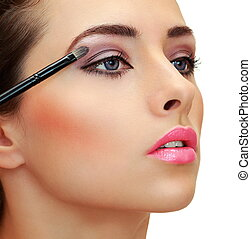Eyes makeup. Brush applying eye shadows on beauty woman...