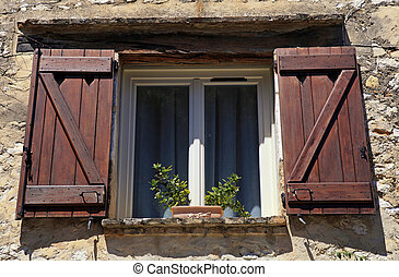 french open window with old wood shutters in stone rural house, Provence, France.