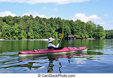Woman Kayaking - Woman kayaking on a beautiful lake.