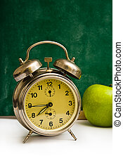 School time again Clock and apples on teachers table, green...