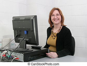teacher at computer - one adult female teacher sitting at...