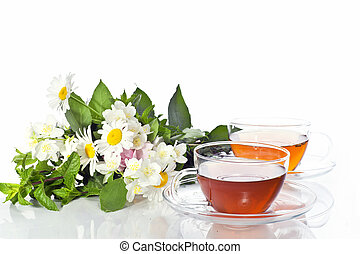 Transparent cup with green tea and fresh herbal bouquet on...