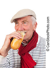 Senior man eating French bread - Portrait senior man with...