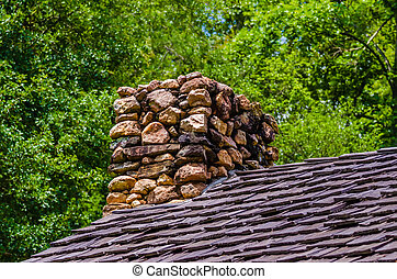Stone Chimney on Rustic Cabin in forest