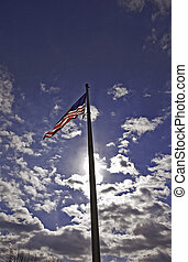 United States Flag - Against a beautiful blue sky and in a...