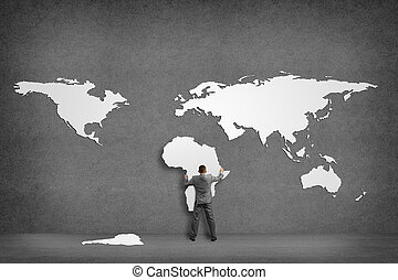 businessman attaches to the wall of the continents, holds...