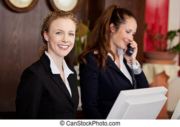 Two women working as professional receptionists - Two young...