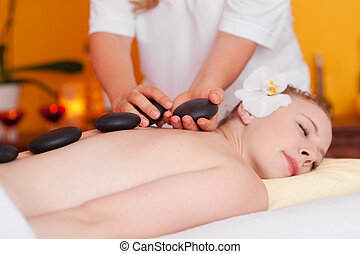 Young woman having a massage with hot stones - Relaxed...