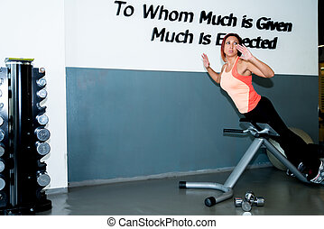 Fitness Female Exercise hear Back - A woman works out at a...