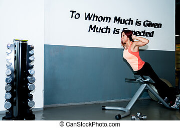 fit woman - A woman works out at a back station in a heath...