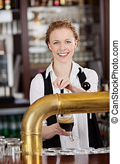 Smiling barmaid serving draft beer - Smiling attractive...