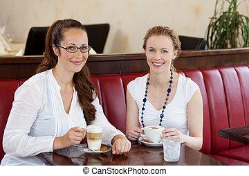 Two beautiful women in a cafe