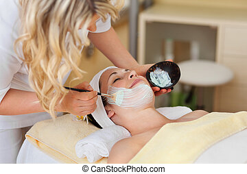 Beautician applying a face mask to a beautiful smiling woman...