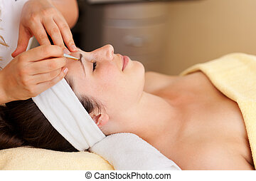Beautiful woman having her eyebrows plucked by a beautician...