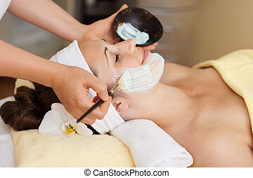 Therapist applying a face mask to a beautiful young woman in...