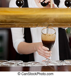 Waitress pouring dark beer - Waitress pouring a pint glass...