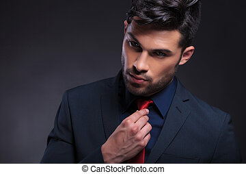 business man adjusts his tie - young business man adjusting...