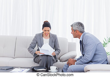 Stressed businesswoman holding documents and businessman...