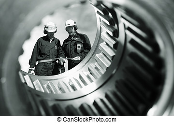 industry workers and gears axles - two industry workers seen...