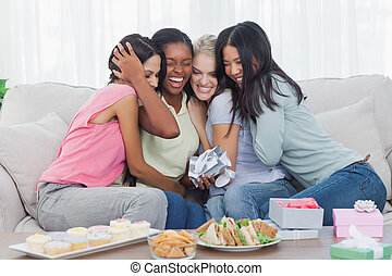 Friends offering gifts and hugging woman during party at...