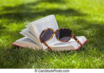 Book on the grass - Book and sunglasses on a green grass