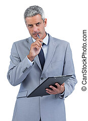 Assiduous businessman holding clipboard and taking notes -...