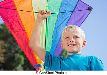 Child raising his arm with a kite in it - Blonde child...