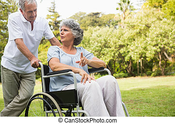 Mature woman in wheelchair speaking with partner in the park...