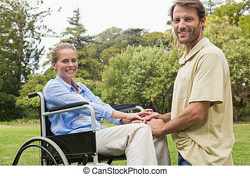 Happy woman in wheelchair with partner kneeling beside her...