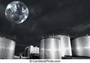 full moon over industry - oil and gas refinery tanks lit by...