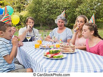 Family celebrating little girls birthday outside at picnic...