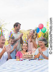 Cheerful extended family clapping for little girls birthday...