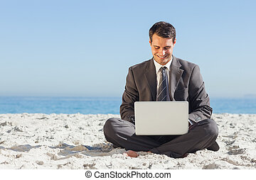 Young businessman with legs crossed typing on his laptop on...