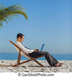 Young businessman on his beach chair using his laptop -...