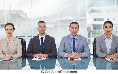 Stern business people sitting straight looking at camera in...