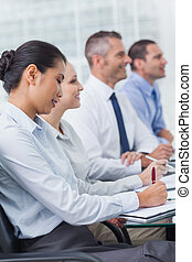 Cheerful employees attending presentation in bright office