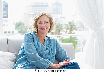 Content blonde woman sitting on her couch smiling at camera...