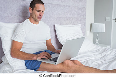 Concentrating man using laptop on bed at home in the bedroom