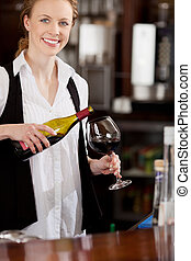 Smiling waitress pouring a glass of red wine - Smiling...