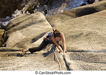 Climbing - A fit and attractive girl climbs a granite rock...