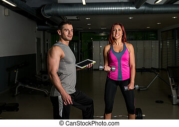 Physical Fitness Trainer in a Gym - young woman exercising...