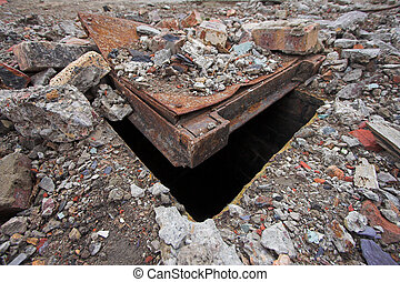 Mantrap - Manhole cover partially buried beneath rubble and...