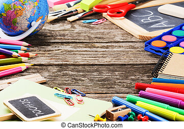 Frame with colorful school supplies on wooden background