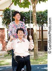 asian senior enjoying swing in the park