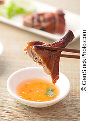 chopstick holding chinese roast duck served with soya sauce...